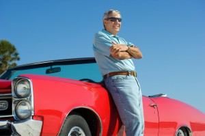 Senior adult on the beach with a restored 1967 convertible GTO
